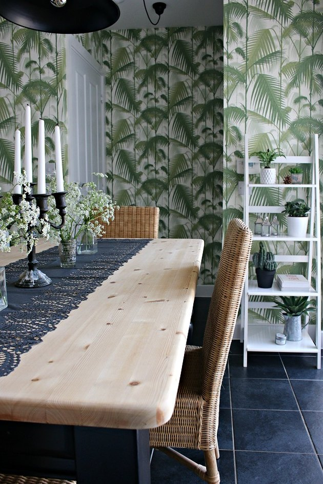 Green boho room with natural wood table and palm leaf wallpaper