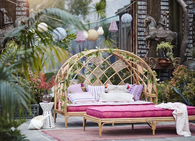 pink and rattan daybed on patio with plants