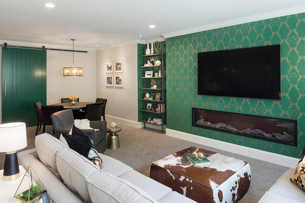 transitional family room with green flocked wall paper, flat screen tv, cowhide pouf, off-white couch.