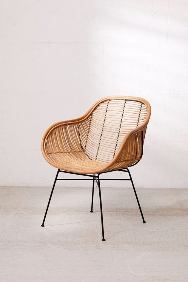 Rattan armchair with thin black metal legs
