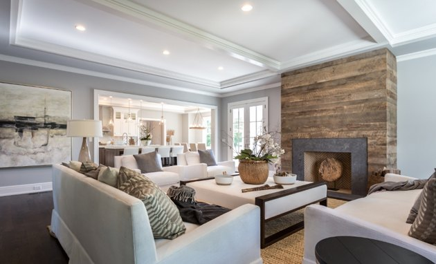 transitional family room with reclaimed wood fireplace, white sectional, side chairs and sofas.