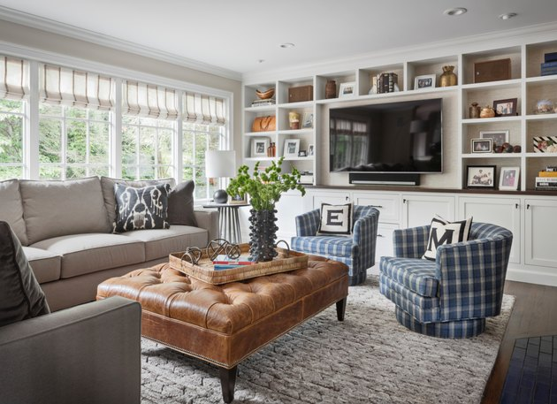 transitional family room with plaid side chairs, leather tufted ottoman, flat screen tv, built in shelves.