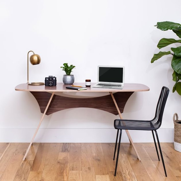 round table with laptop near black chair