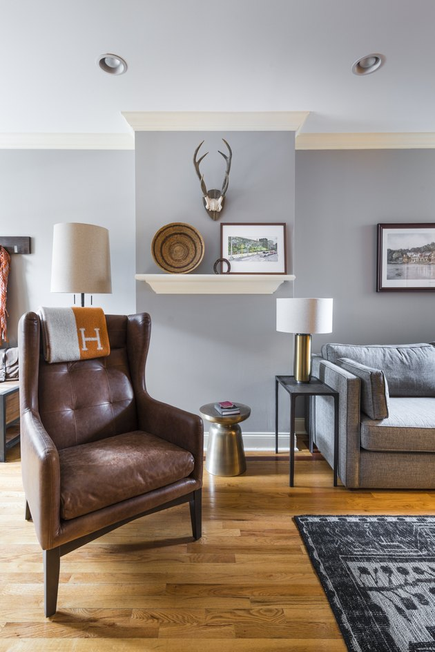 transitional family room with high back leather chair, gray couch, wood floors, side table, lamp, shelf with art and basket, antlers on wall.