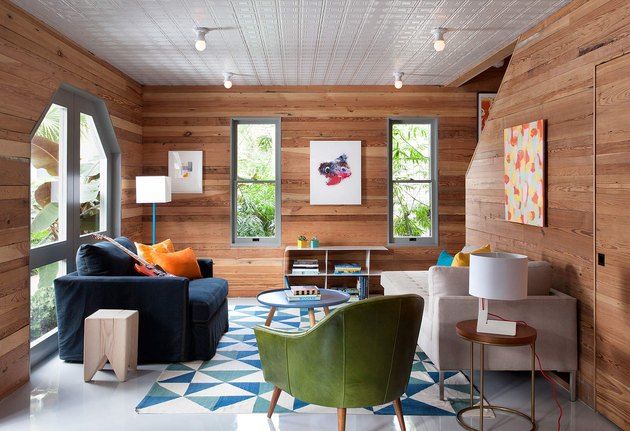 transitional family room with overstuffed and modern sofas, green side chair, blue patterned rug, wood paneled walls, art.