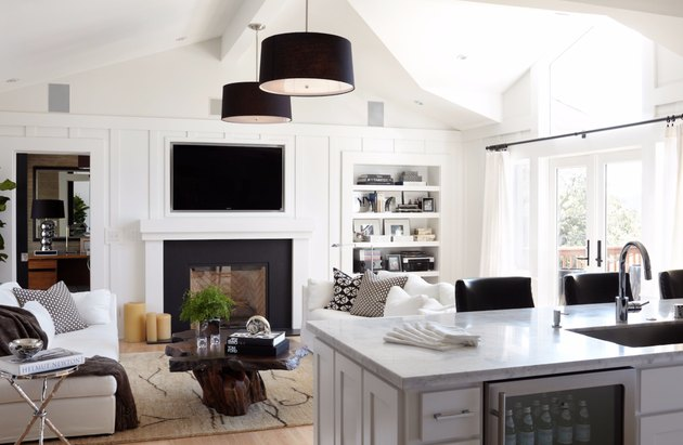 transitional family room with two matching black pendant lamps, white sofas, built in flat screen tv and shelving, fireplace, hard wood floors.