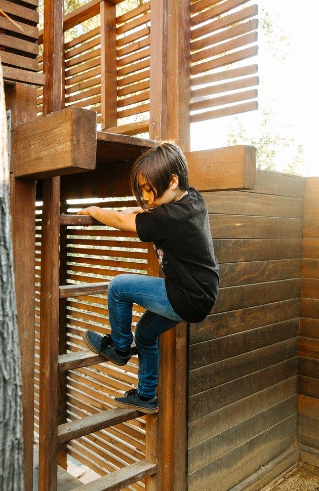 Boy descending modern treehouse ladder