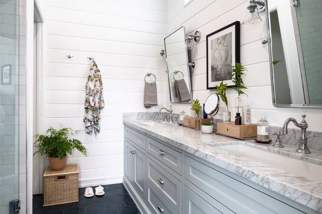 bathroom with white shiplap wall, two sink bathroom vanity, light grey cabinetry and mirrors
