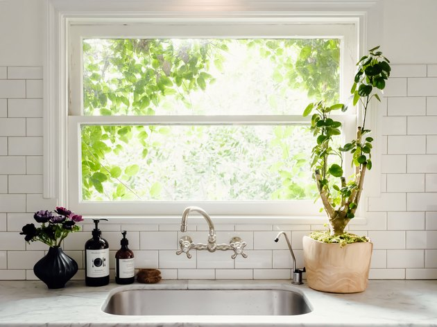 view of kitchen sink, double handle faucet and window with view of greenery