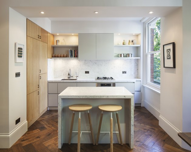small mitred marble kitchen island in contemporary kitchen with herringbone floor