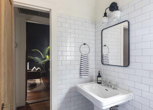 bathroom pedestal sink, subway tile wall tile, mirror and light fixture above