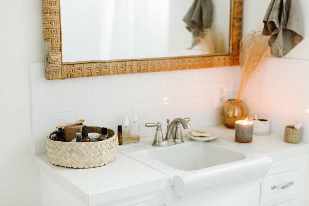 small white sink, wicker basket and lit candle