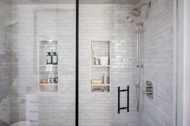 close up view of shower with subway tile walls and built-in storage