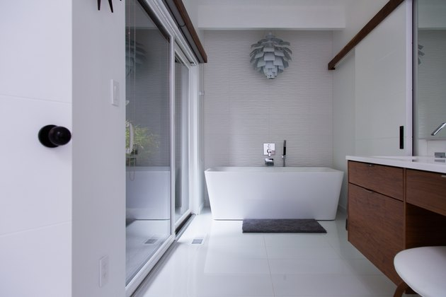 large bathroom with freestanding bathtub, decorative pendant light fixture above the tub, wood vanity with ceramic top, large walk-in shower with glass door