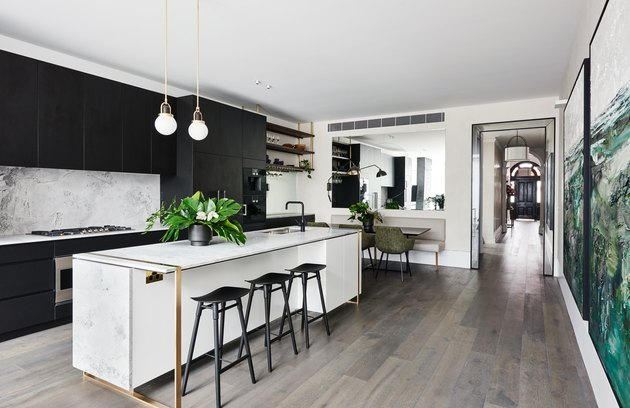 dolomite marble kitchen island with brass details in kitchen with black cabinets