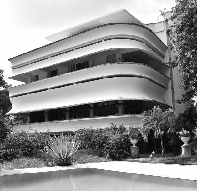 Modernist building with streamlined balconies and white exterior