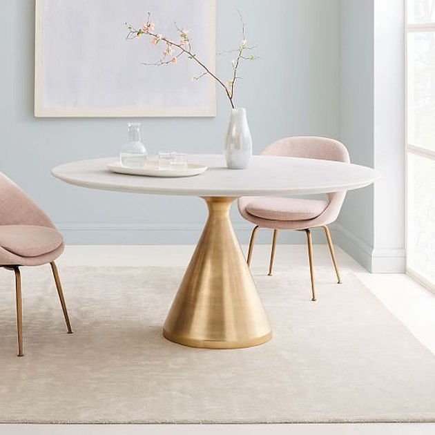 Minimalist dining room idea with white marble oval dining table with brass pedestal and blush midcentury chairs