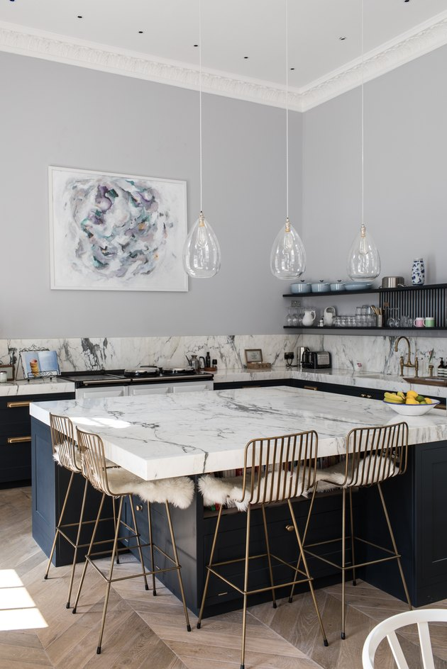 chunky marble kitchen island with gold wire seating