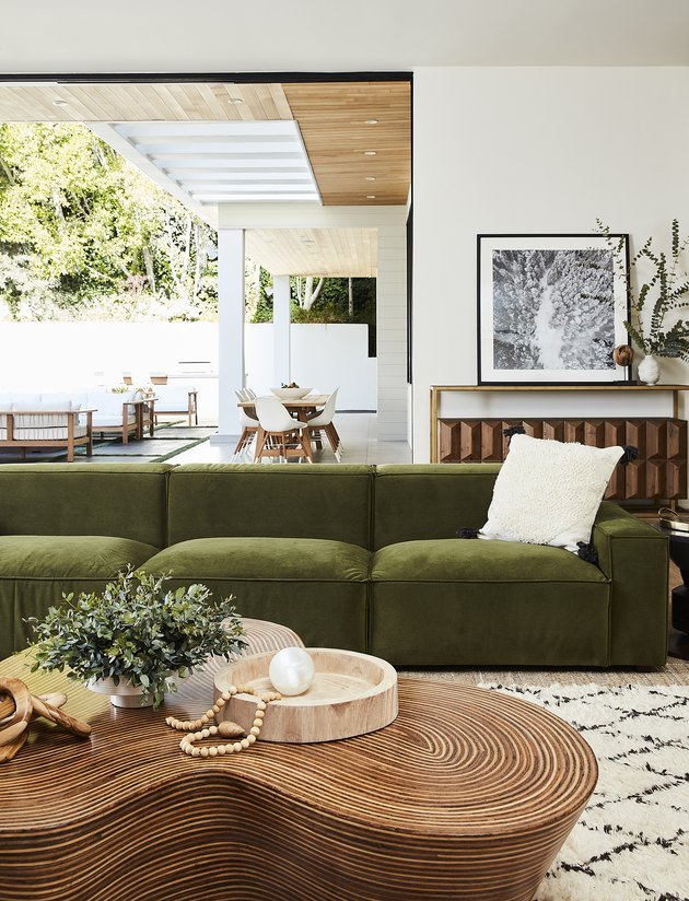 boho green room with luxe velvet sofa and wood coffee table