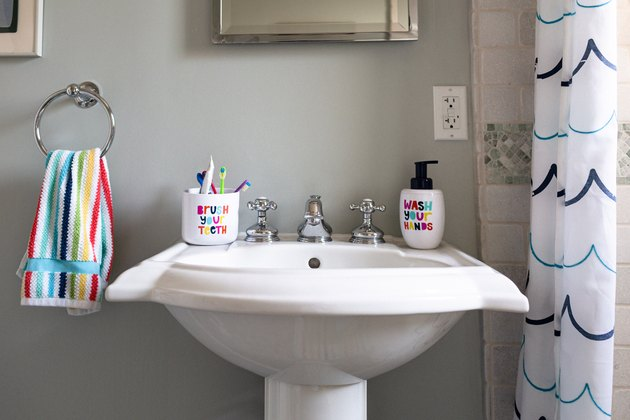 white pedestal sink, rainbow striped hand towel hung up, a toothbrush holder that says brush your teeth, a soap dispenser that says wash your hands