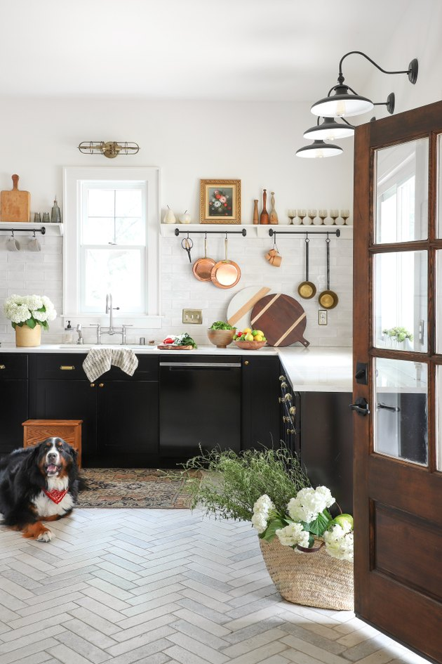 dark kitchen cabinets with light floors and hanging copper pots