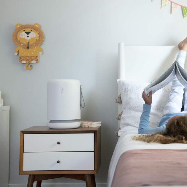 White cylindrical air purifier on bedside table