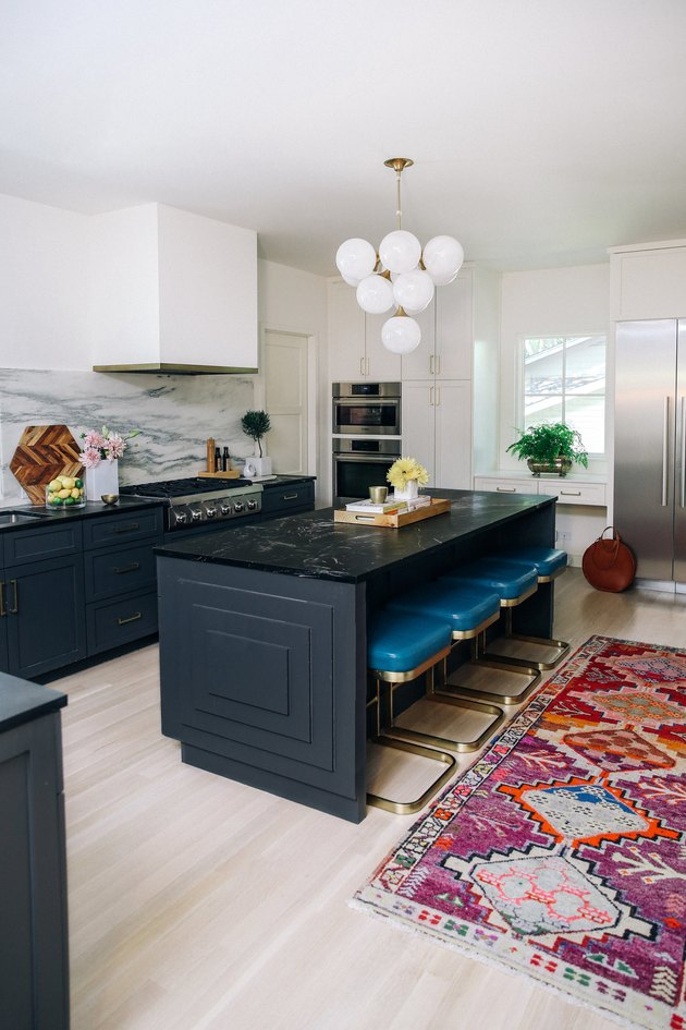 black marble kitchen island with teal barstools and printed kitchen rug