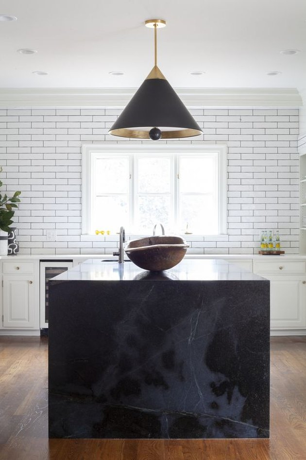 black and gray marble kitchen island with black cone-shaped pendant lights