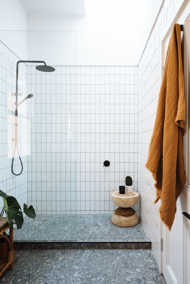 white shower storage ideas with terrazzo floor and wood stool
