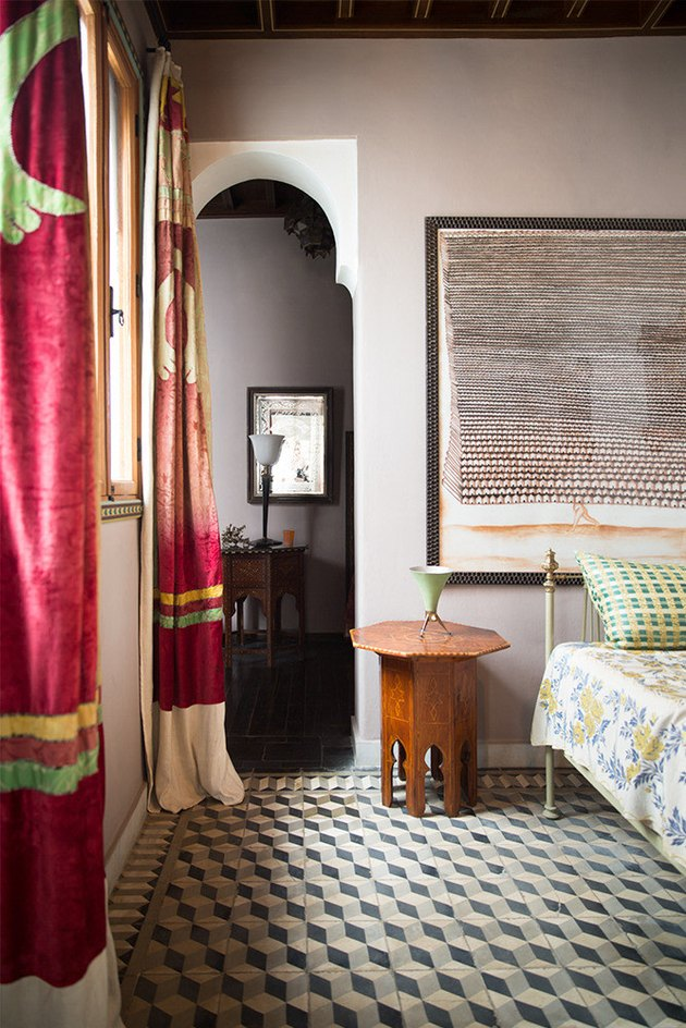 pattern filled bedroom with moroccan textiles and vintage wood table
