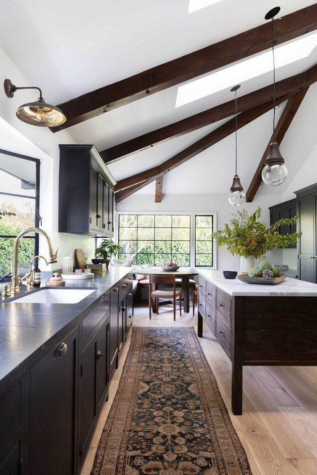 dark kitchen cabinets with light floors and a patterned kitchen runner