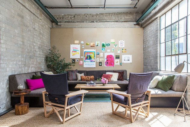 family room furniture with pink pillows and exposed brick wall