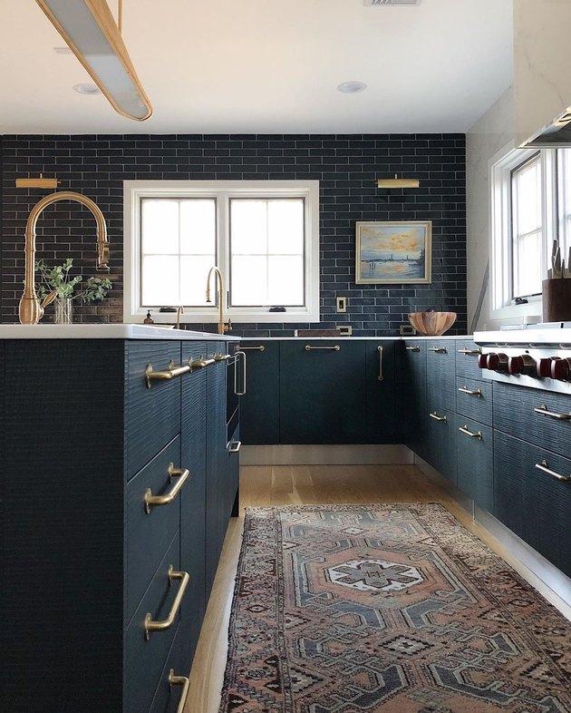 dark kitchen cabinets with light floors with blue subway tile backsplash and light wood floors