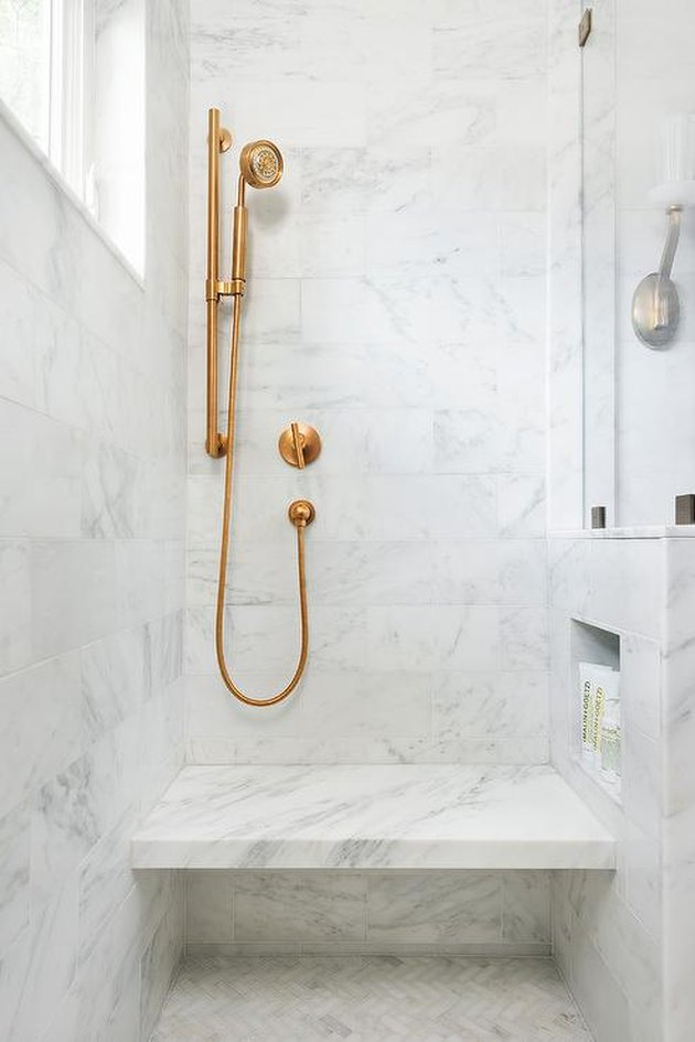 marble bathroom with brass fixtures and shower storage ideas and shower bench
