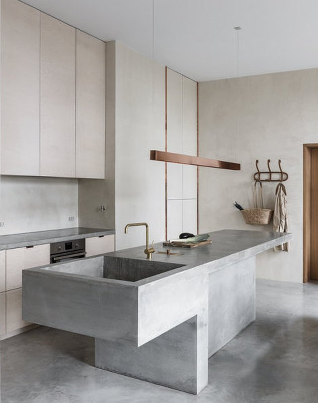 concrete minimalist kitchen sink in kitchen with copper light fixture and concrete floor