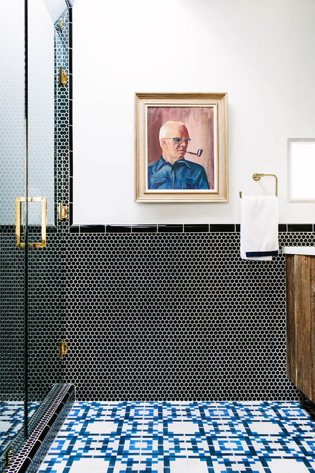 bold bathroom tile with brass accents, reclaimed wood vanity and vintage oil painting