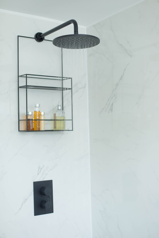 marble shower storage ideas with black fixtures and shower caddy