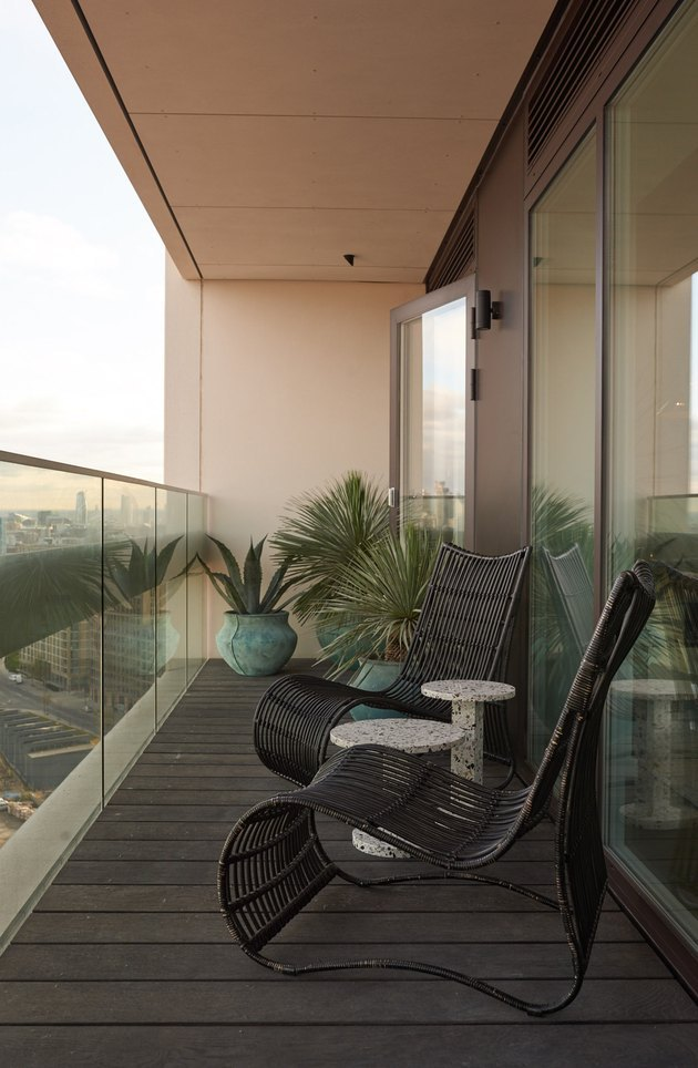 minimalist balcony idea with two black chairs and plants