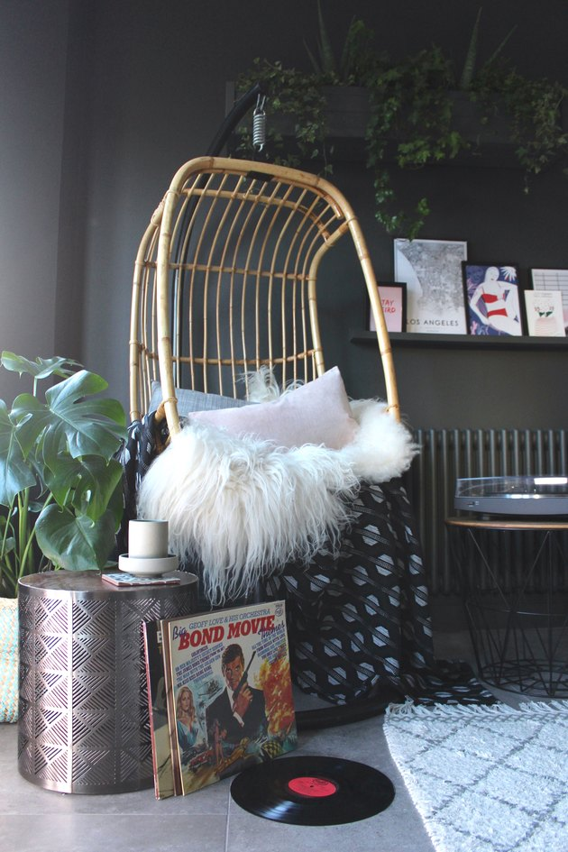 hanging rattan chair in dark gray living room corner idea
