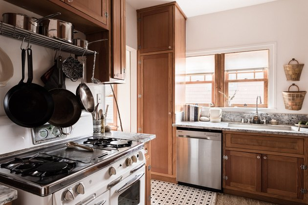 kitchen with natural wood cabinets, old gas stove, hanging cast-iron pans, dishwasher and sink