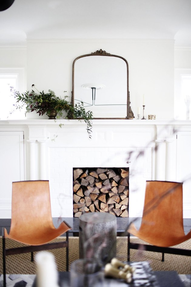 living room mirror ideas with fireplace filled with chopped wood and leather chairs