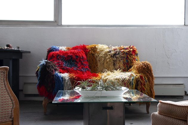 Colorful afghan covered couch with mirrored table