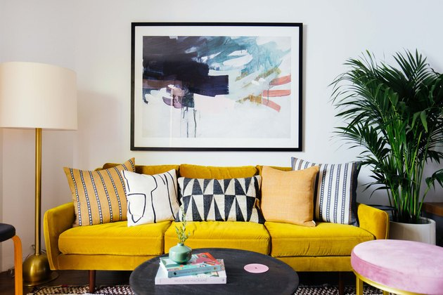 Yellow modern sofa in living room with floor lamp and artwork