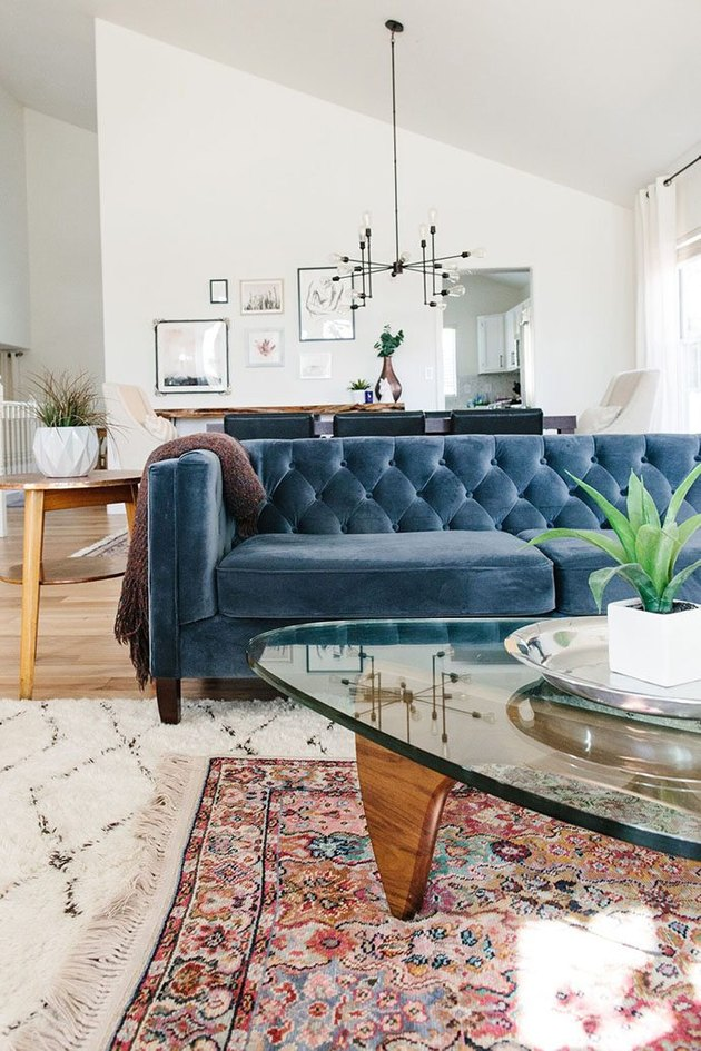 living room with blue tufted sofa and layered area rugs