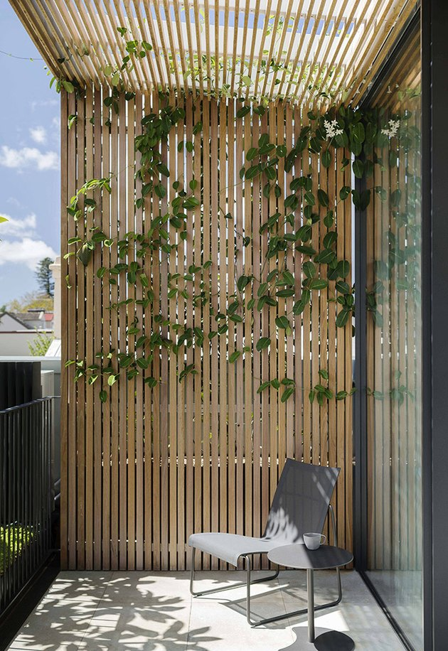 minimalist balcony idea with wood slat frame and modern chair and side table