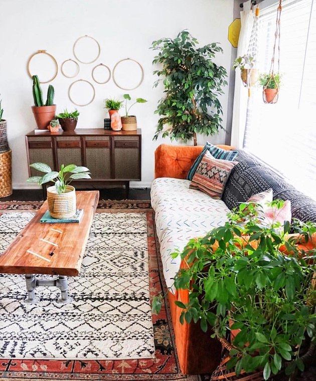 pattern-filled living room with lots of plants and orange sofa