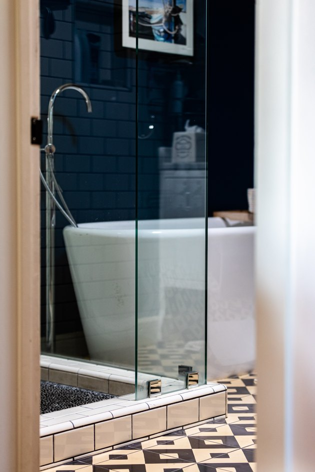 freestanding white tub with a floor-mounted faucet, blue wall, black and white tiled floor, glass shower door