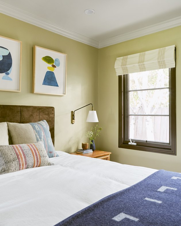 Bold small master bedroom idea in colorful space with artwork above bed