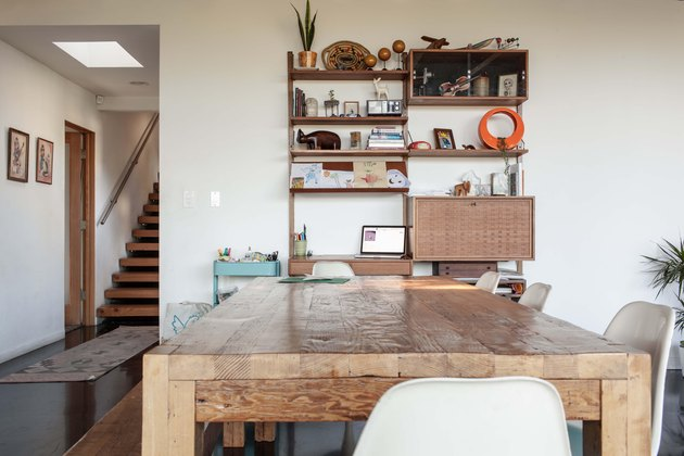 Large dining table made from reclaimed wood acts as living room centerpiece