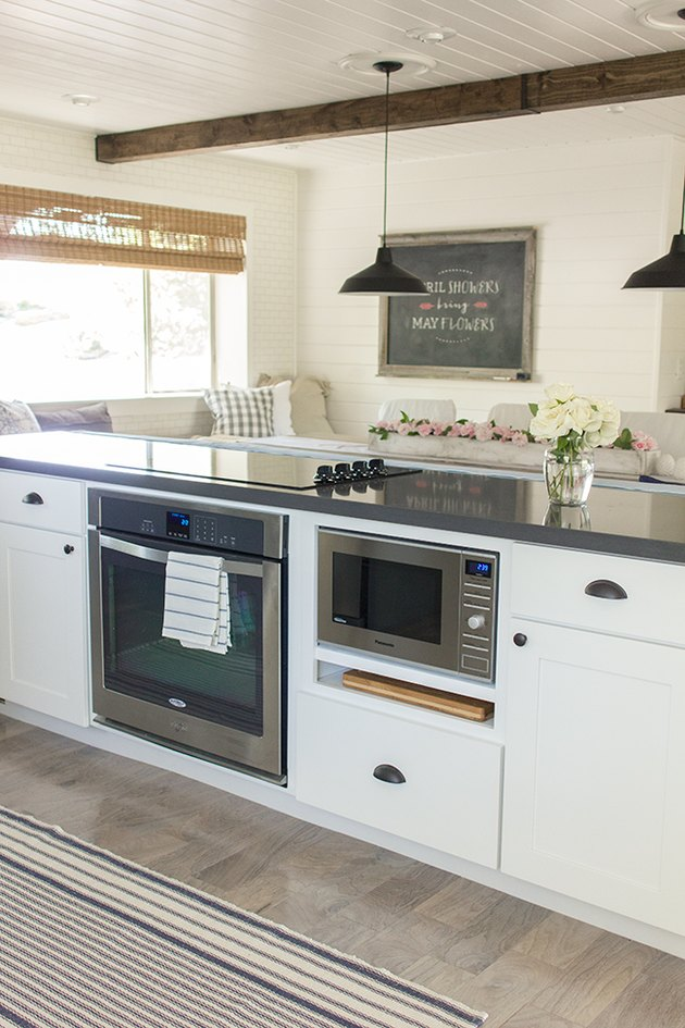 White cabinets on kitchen island with built in microwave, induction stove, black pendants lights, gray wood floor.